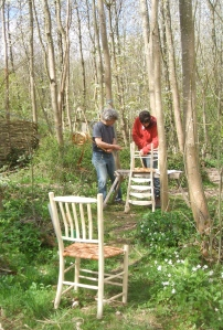Hans and Fransisco applying wych elm bark to their chairs, surrounded by spring flowers.